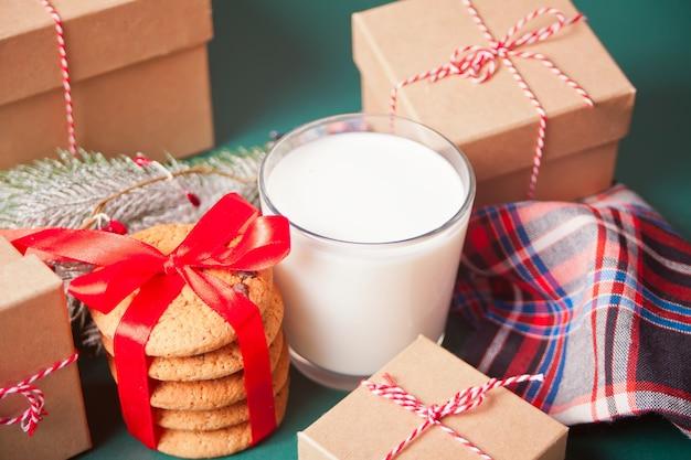 Glas milch, plätzchen, weihnachtsgeschenkboxen und kiefer verzweigen sich auf die grüne tabelle