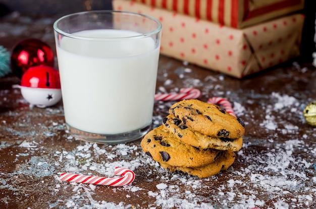 Glas milch und hausgemachte kekse mit schokolade auf dem tisch, weihnachtsdekorationen, winterferienkonzept, grußkartenvorlage, platz für ihren text,