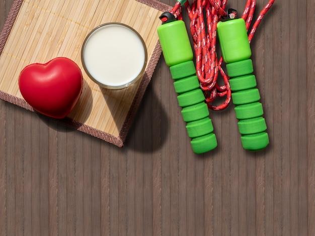 Glas milch und herz auf hölzernem hintergrund. trinken für gesundheit und fitness