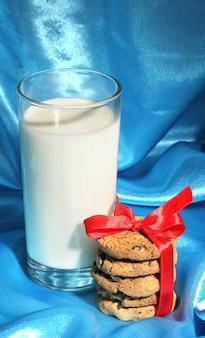 Glas milch und kekse auf blauem stoffhintergrund
