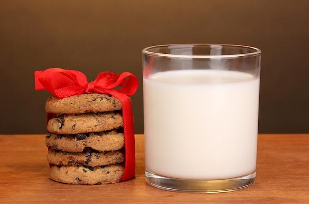 Glas milch und kekse auf holztisch auf brauner oberfläche