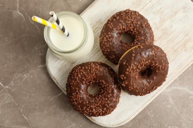 Glas milch und leckere donuts auf grauem tisch