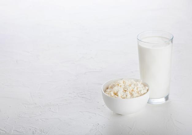 Glas milch und schüssel hüttenkäse auf weißem steinküchentisch.