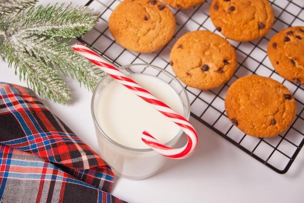 Glas milch, zuckerstange, hausgemachte kekse für den weihnachtsmann