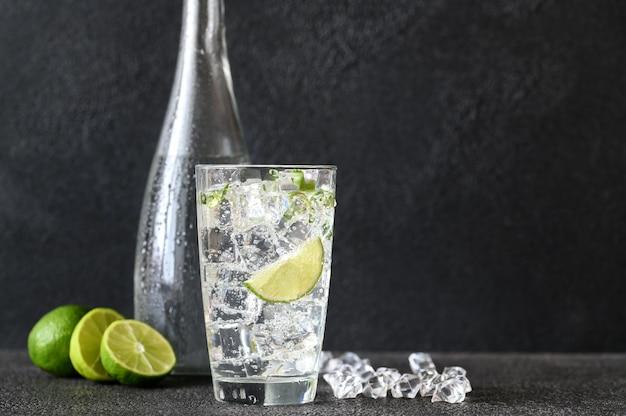 Glas mineralwasser mit eiswürfeln und limettenscheibe