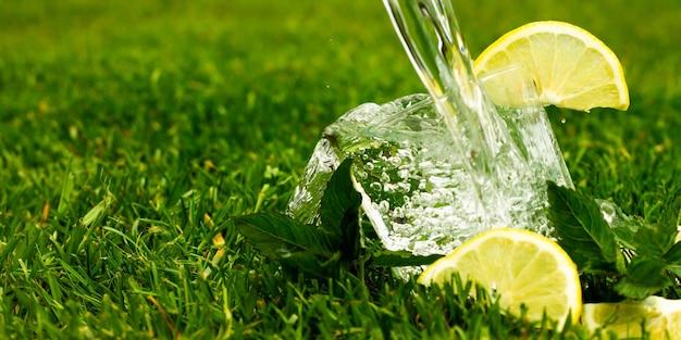 Glas mineralwasser oder limonade mit zitronen- und minzblättern. wasser mit spritzern und tropfen fließt in ein glas. banner.
