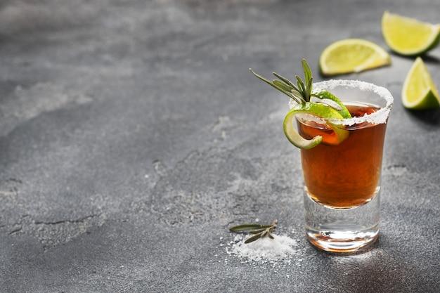 Glas mit alkohol, salz und kalk auf einem dunklen betonhintergrund.