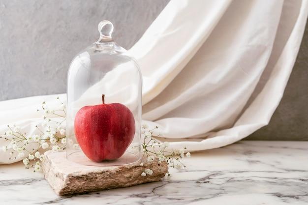 Glas mit apfel und blumen daneben