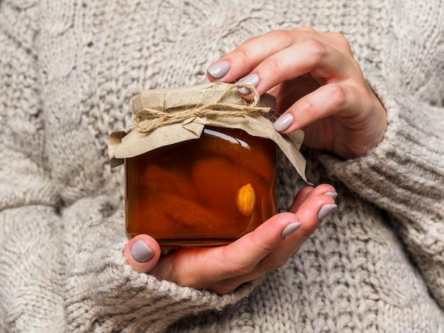 Glas mit aprikosenmarmelade in den händen einer frau