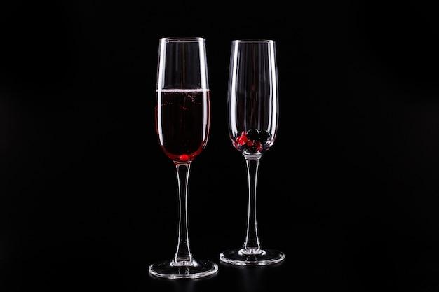 Glas mit beeren und rotem champagneralkoholcocktail steht auf schwarzem hintergrund