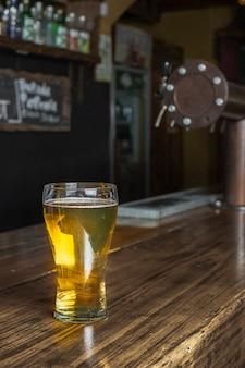 Glas mit bier an der bar auf dem tisch