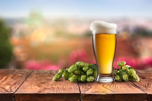 Glas mit bier mit hopfen auf einem holztisch