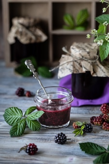 Glas mit blackberry sauce nahaufnahme. zweig mit beeren und blättern in einer geschnitzten holzkiste auf einem dunklen holz