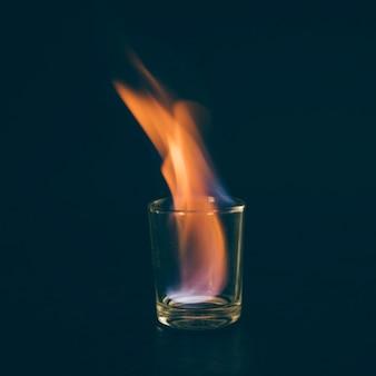 Glas mit brennendem alkohol auf schwarzem hintergrund
