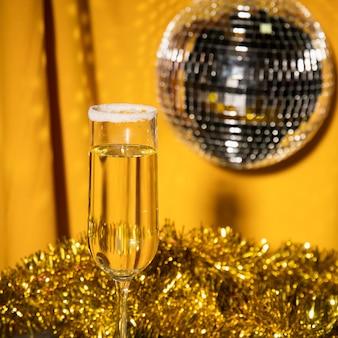 Glas mit champagner und silberner partykugel