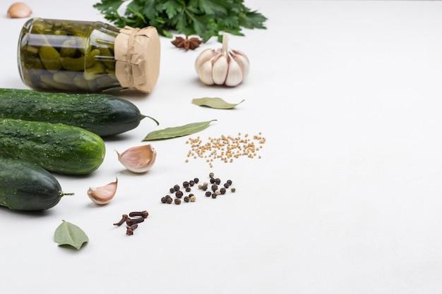Glas mit dosengurken, frischen gurken, grüner petersilie, knoblauch und gewürzen. hausgemachte fermentationsprodukte. gesunde winterlebensmittel. weiße oberfläche. speicherplatz kopieren