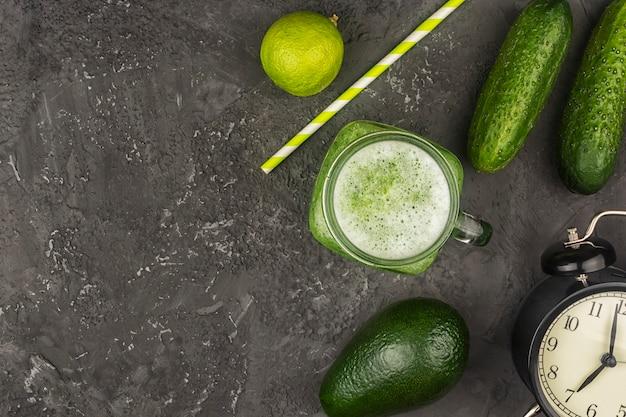 Glas mit einem gurken-smoothie. frisch gepresster gurkensaft mit limette und avocado. flach liegen mit kopierraum, zutaten.