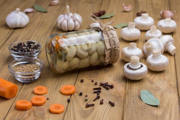 Glas mit eingemachten pilzen und frischen champignonpilzen gewürz knoblauchzwiebel lorbeerblatt auf tisch