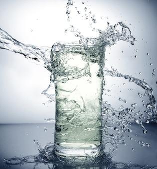 Glas mit eis und flüssigem spritzen