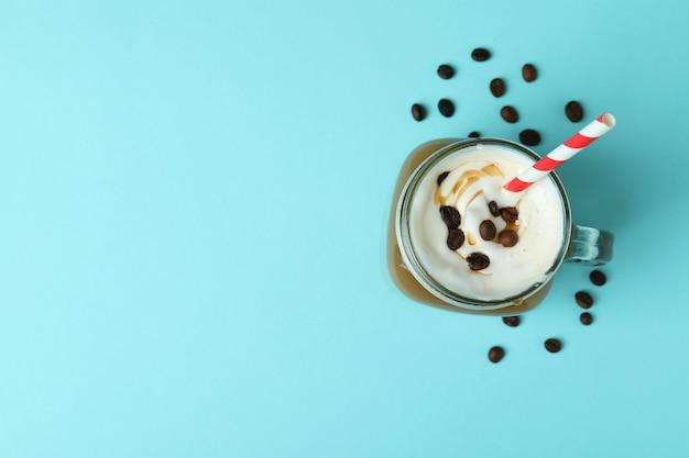 Glas mit eiskaffee und bohnen auf blauem hintergrund