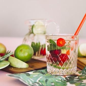 Glas mit erdbeeren goss wasser nahe früchten auf hackendem brett ein