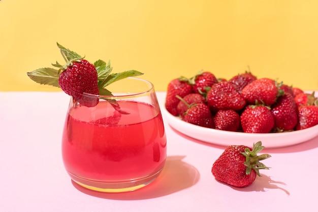 Glas mit erdbeerlimonade und einem teller erdbeeren auf gelbem und rosa hintergrund in hellem licht, sommerkonzept, nahaufnahme.