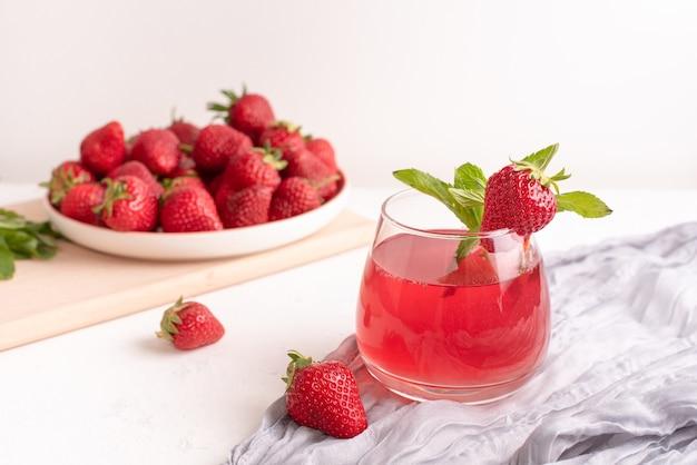 Glas mit erdbeerlimonade und erdbeeren auf einem tisch mit textilien auf weißem hintergrund, sommergetränkekonzept, nahaufnahme.
