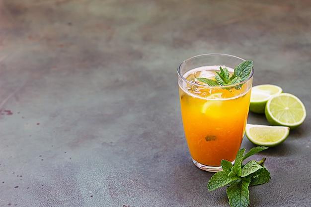 Glas mit erfrischungscocktail mit aprikose, minze und limette. kalter cocktail oder eistee.