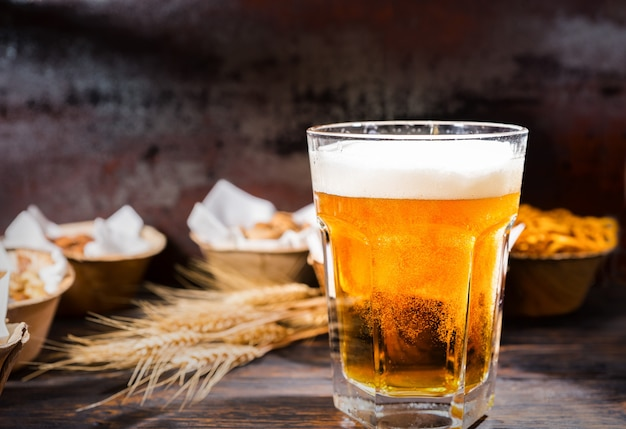 Glas mit frisch eingegossenem bier in der nähe von tellern mit pistazien, kleinen brezeln und erdnüssen auf dunklem holzschreibtisch. lebensmittel- und getränkekonzept