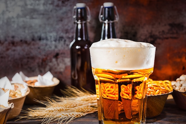 Glas mit frisch eingegossenem bier und großem schaum in der nähe von flaschen, weizen und tellern mit snacks auf dunklem holzschreibtisch. lebensmittel- und getränkekonzept