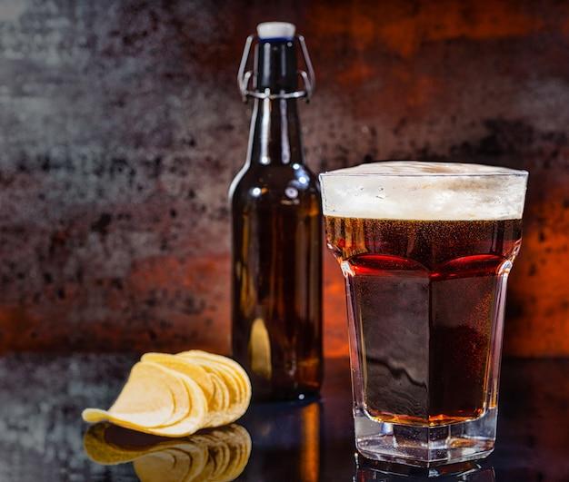 Glas mit frisch gegossenem dunklem bier, bierflasche in der nähe von verstreuten leckeren pommes auf einer schwarzen spiegeloberfläche. lebensmittel- und getränkekonzept