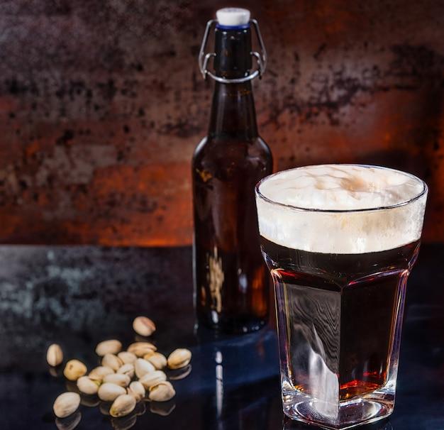Glas mit frisch gegossenem dunklem bier, bierflasche in der nähe von verstreuten pistazien auf einer schwarzen spiegeloberfläche. lebensmittel- und getränkekonzept