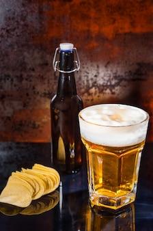 Glas mit frisch gegossenem hellem bier, bierflasche in der nähe von verstreuten pommes auf einer schwarzen spiegeloberfläche. lebensmittel- und getränkekonzept
