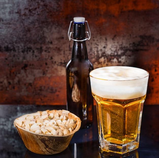 Glas mit frisch gegossenem hellem bier, bierflasche nahe holzteller mit pistazien auf einer schwarzen spiegeloberfläche. lebensmittel- und getränkekonzept