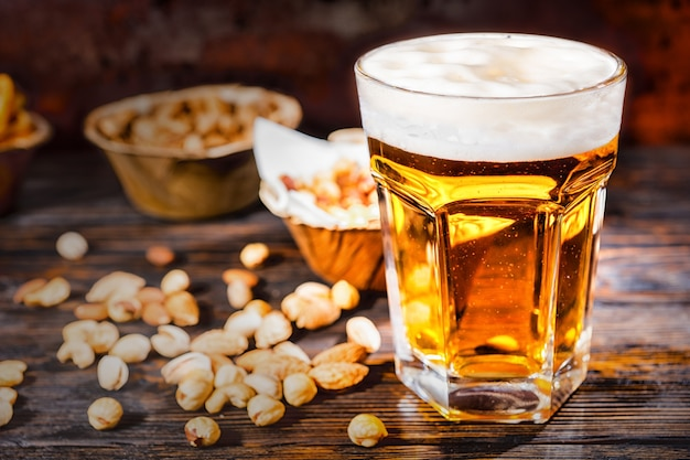 Glas mit frisch gegossenem hellem bier in der nähe von tellern mit snacks und verstreuten nüssen auf einem dunklen holzschreibtisch. lebensmittel- und getränkekonzept