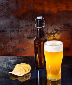 Glas mit frisch gegossenem, ungefiltertem hellem bier, bierflasche in der nähe von verstreuten chips auf einer schwarzen spiegeloberfläche. lebensmittel- und getränkekonzept