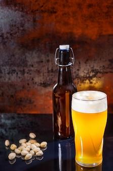 Glas mit frisch gegossenem ungefiltertem hellem bier, bierflasche in der nähe von verstreuten pistazien auf einer schwarzen spiegeloberfläche. lebensmittel- und getränkekonzept