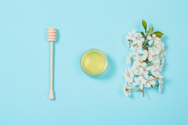 Glas mit frischem honig und einem hölzernen schöpflöffel und einem zweig eines apfelbaums mit weißen blumen auf einem blauen hintergrund. flache lage, draufsicht
