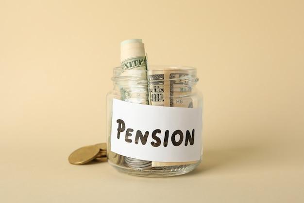Glas mit geld und inschrift pension auf beiger oberfläche