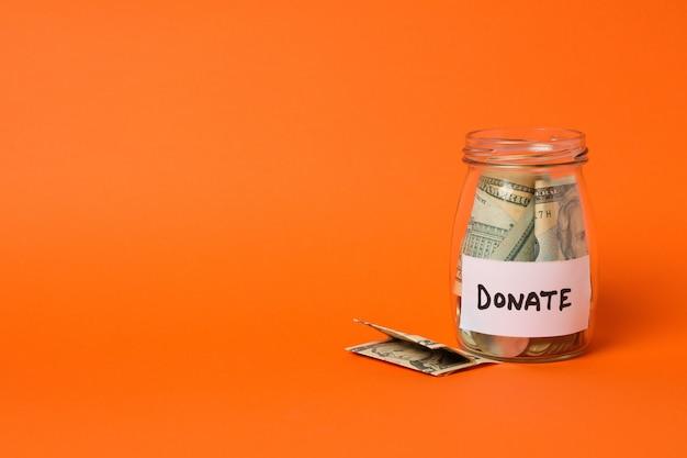 Glas mit geld und text spenden auf orange hintergrund