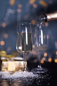 Glas mit getränk an bord in der nähe von ornament schnee und geschenkbox