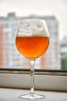 Glas mit getränk, glas auf einem bein, glas mit bier am fenster