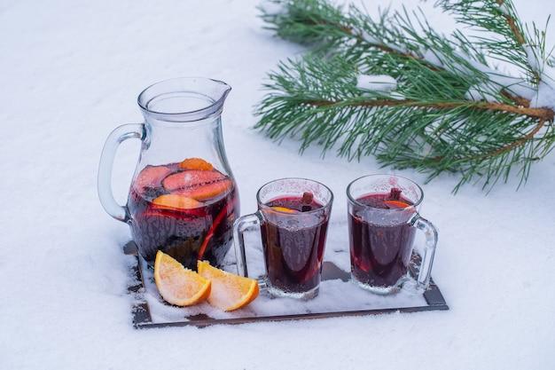 Glas mit glührotwein auf einem bett des schnees und des weißen hintergrunds. glühwein oder punsch mit orangen- und anisstern und zimt, nahaufnahme. weihnachtsgetränk.