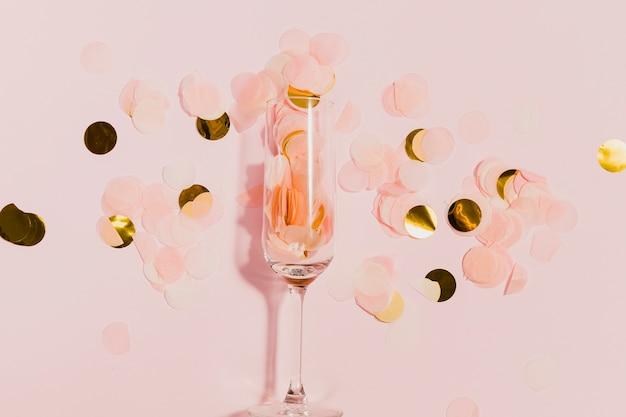 Glas mit goldenen konfetti auf silvesterparty