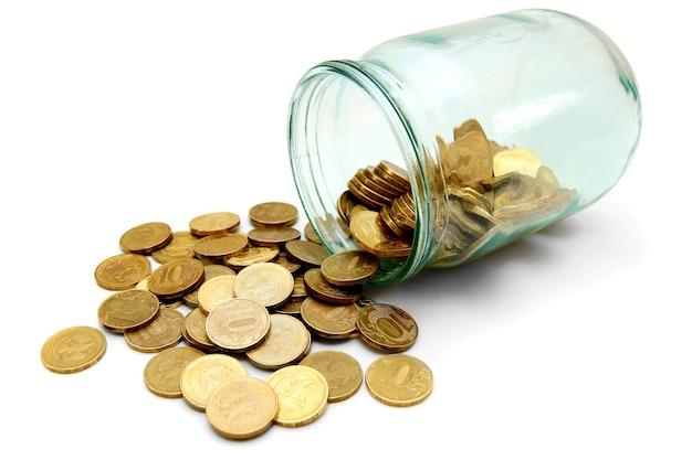 Glas mit goldmünzen. auf einem weißen tisch.