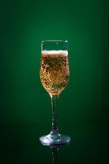 Glas mit hellem bier auf einem grün.