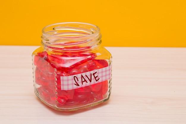Glas mit herzen auf dem tisch mit sicherer inschrift