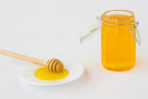 Glas mit honig auf einem weißen tisch. honigschöpflöffel auf weiß