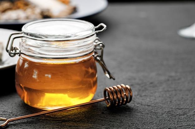 Glas mit honig auf schwarzem tisch nah oben