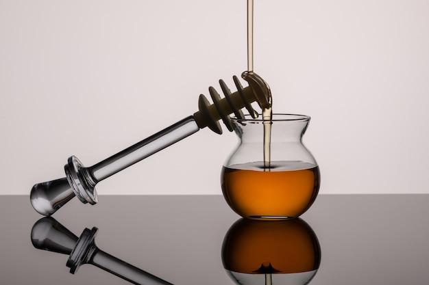 Glas mit honig fließt hinein, ein stock für honig auf einem studiohintergrund. nahansicht. speicherplatz kopieren.